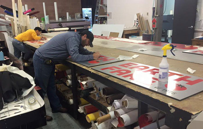 Men fabricating signs.
